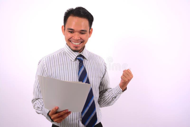 成功的亚洲bussinessman,非常愉快的看看白皮书 免版税库存图片
