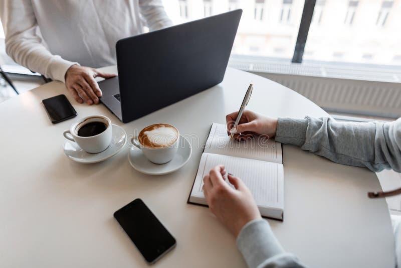 成功的人主任举行与年轻女人的一个业务会议 与公司业务经理的面试在办公室 免版税库存照片