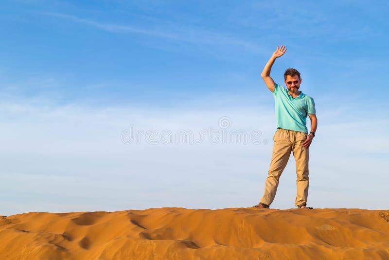 成功的人在沙漠摇从沙丘上面的一只手 免版税库存照片