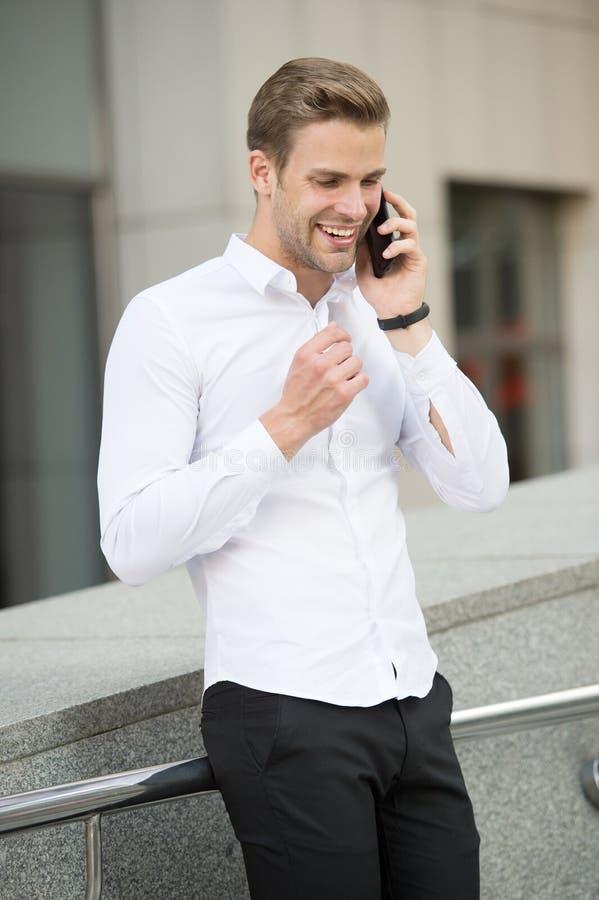 成功的企业电话 要求信息 称的商人客户举行智能手机都市背景defocused 人 库存照片