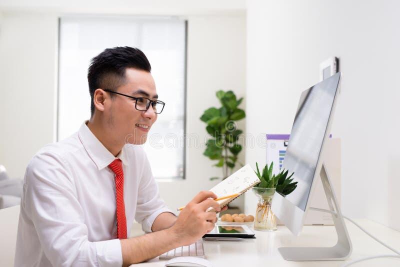 成功的商人与计算机一起使用在办公室 图库摄影