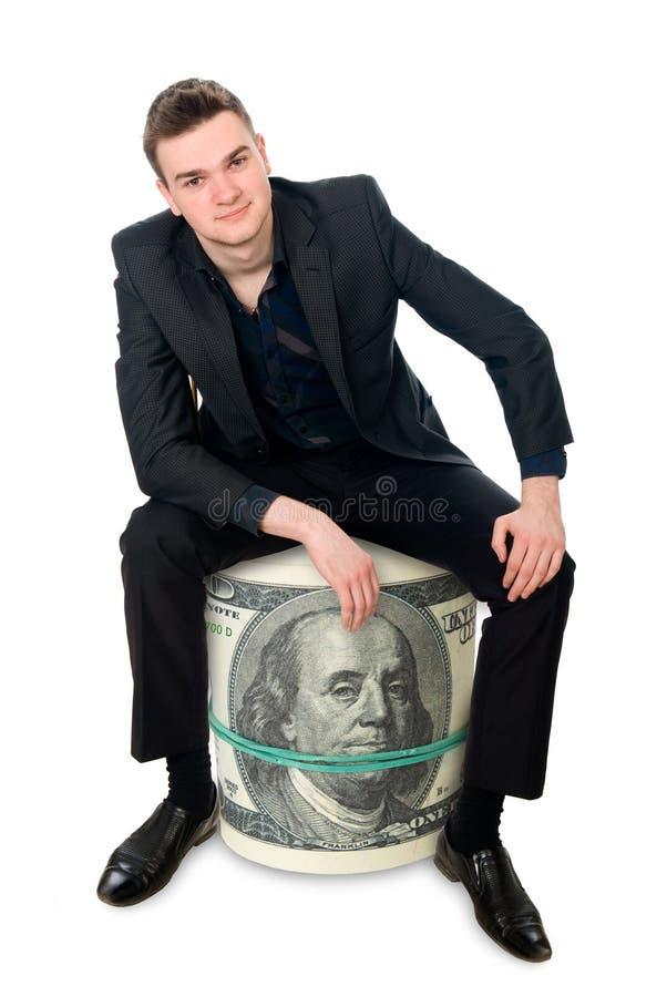 年轻成功的商人坐金钱卷。 免版税库存照片