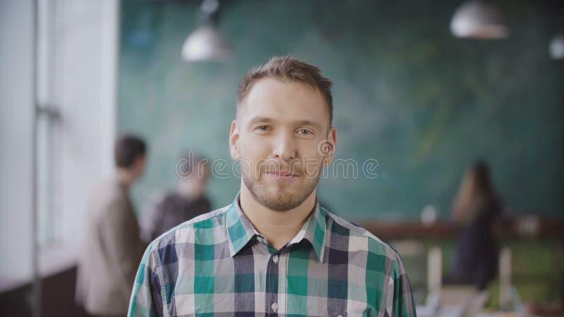 年轻成功的商人画象在繁忙的办公室 看照相机和微笑的英俊的男性雇员 免版税图库摄影