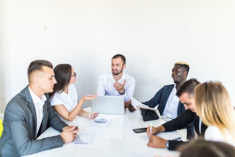 成功的团队负责人和企业主主导的非正式机构内部的业务会议 研究在前景的膝上型计算机的商人 图库摄影