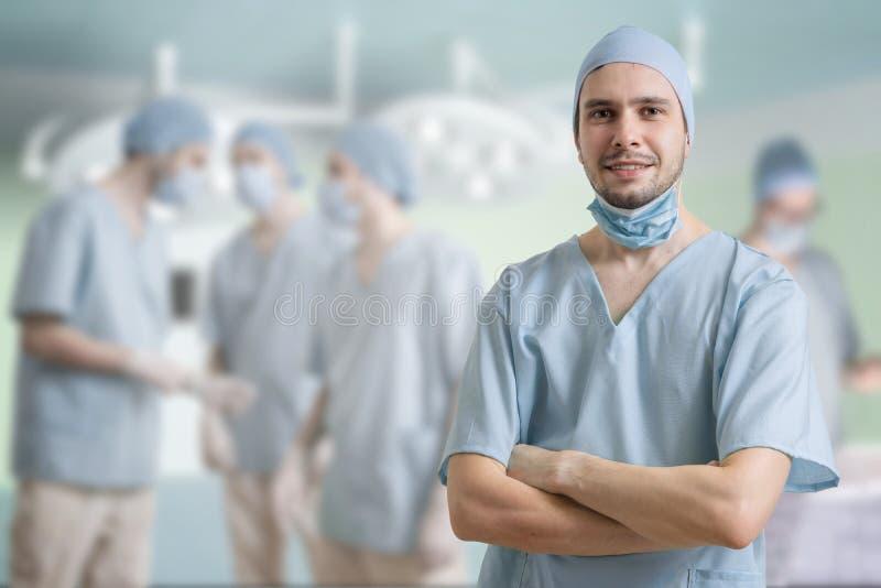 成功的外科医生微笑着 很多外科医生在背景中 免版税库存照片