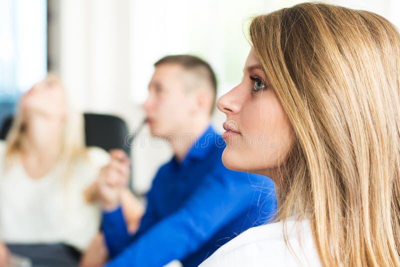 年轻成功的女商人在有同事的办公室在 免版税图库摄影