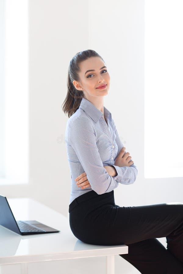 成功的女商人坐书桌在办公室背景中 免版税库存照片
