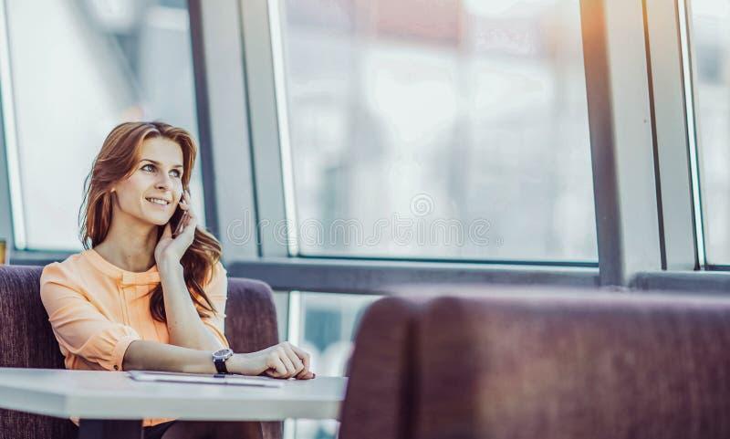 成功的女商人谈话在智能手机一会儿sittin 免版税库存图片