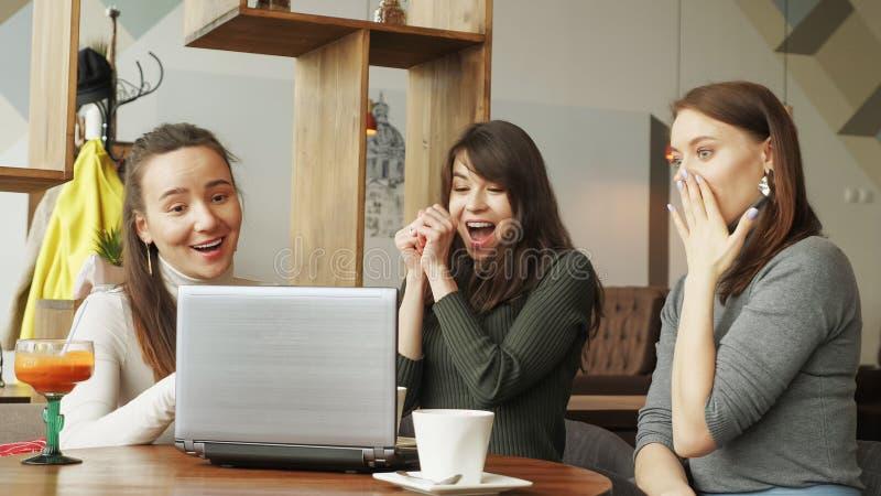 成功的女队在coworking的中心:读与喜讯的一则消息在膝上型计算机一然后给五其中每一 库存图片