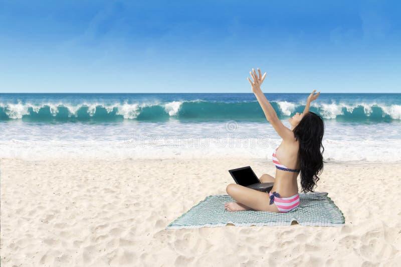 成功的妇女与膝上型计算机一起使用在海滩 图库摄影