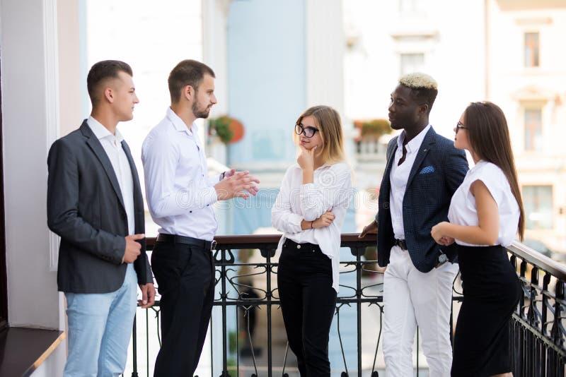 成功的年轻不同种族的商人是谈话和微笑在咖啡休息期间在办公室 免版税库存图片