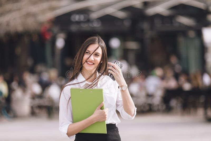 成功的年轻企业微笑的妇女说在室外的电话里 免版税库存图片