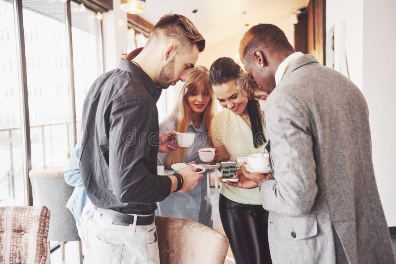 成功的年轻商人是谈话和微笑在咖啡休息期间在办公室 免版税库存照片