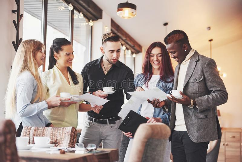 成功的年轻商人是谈话和微笑在咖啡休息期间在办公室 免版税库存图片
