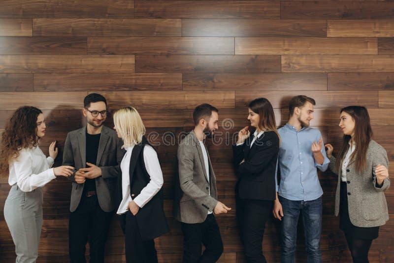 成功的年轻商人是谈话和微笑在咖啡休息期间在办公室 库存照片