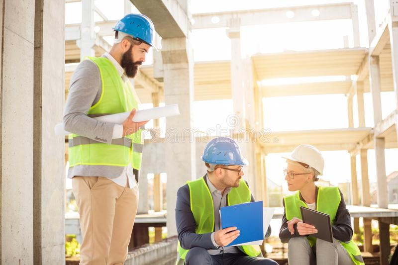 成功的年轻建筑师和开的商务伙伴队关于工地工作的一次非正式会议 免版税库存图片