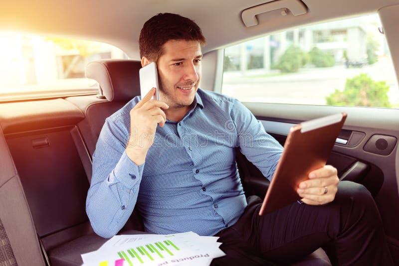 成功的微笑的商人谈话在电话,当坐在汽车后座使用片剂时 免版税库存照片