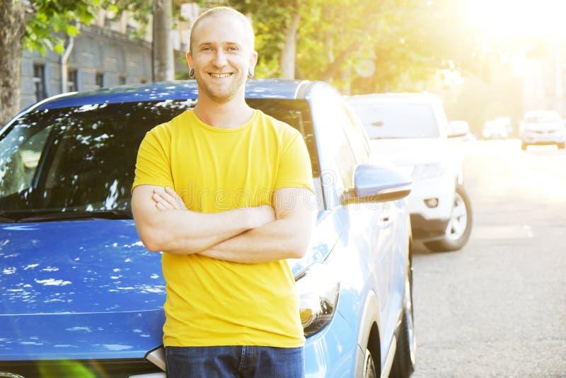成功的愉快的年轻人和他的汽车在软的日落在urbanistic背景点燃 有车的Busines人在路旁 库存图片