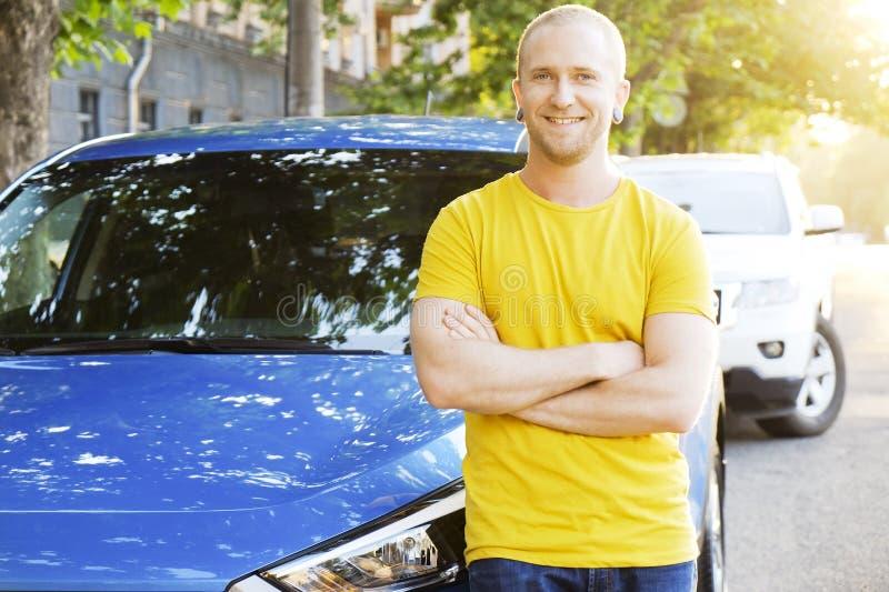 成功的愉快的年轻人和他的汽车在软的日落在urbanistic背景点燃 有车的Busines人在路旁 免版税图库摄影