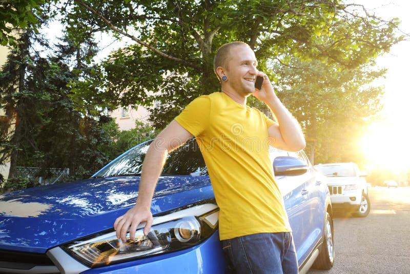 成功的愉快的年轻人和他的汽车在软的日落在urbanistic背景点燃 有车的Busines人在路旁 免版税库存图片