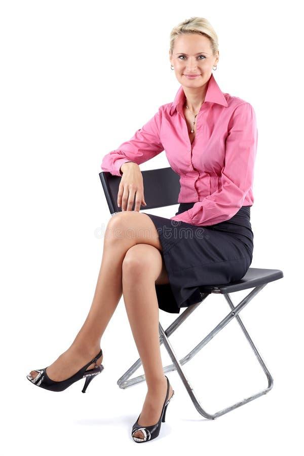 成功的成熟的商业妇女坐在白色背景的一把黑椅子 库存照片