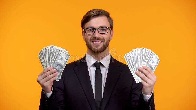 成功的有钱人陈列束美元在手上,在互联网上的容易的收入 免版税图库摄影