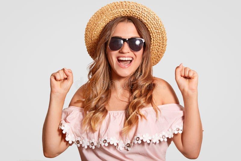成功的极度高兴的女性模型室内射击握紧牙,高兴暑假,准备好移动海外,穿草帽 免版税库存照片