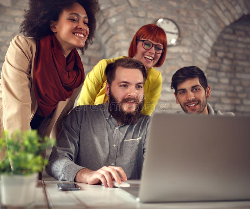 成功的欢呼在计算机的配合年轻网设计师 库存照片