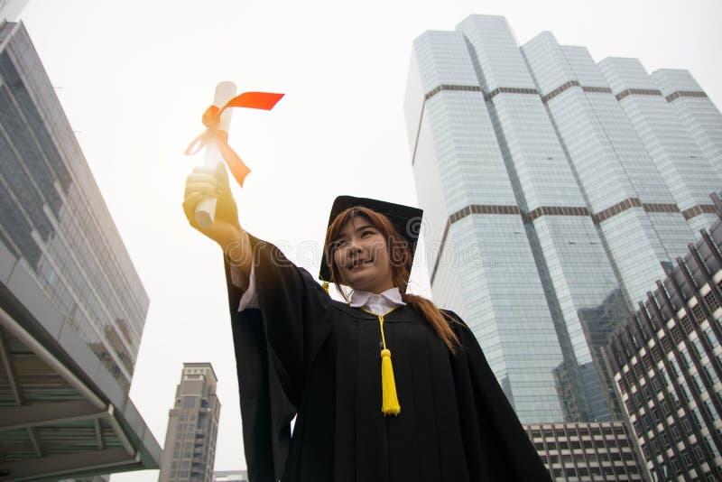 成功的毕业生女学生佩带的盖帽和g画象  免版税图库摄影