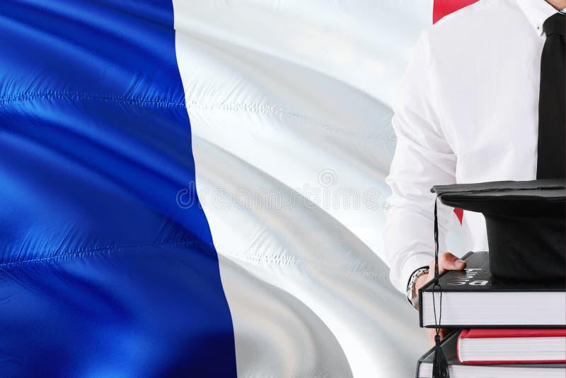 成功的法国学生教育概念 拿着书和毕业盖帽在法国旗子背景 免版税库存图片