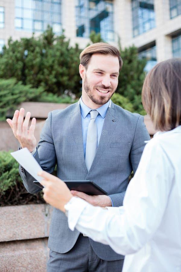 成功的男性和女性商人谈话在办公楼前面,有会议和谈论 库存照片
