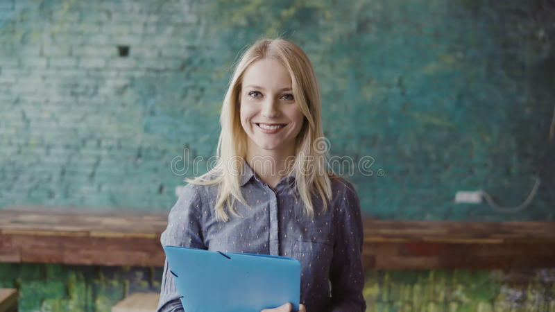成功的美丽的白肤金发的女实业家画象顶楼coworking的空间的 女性拿着本文,微笑 库存照片