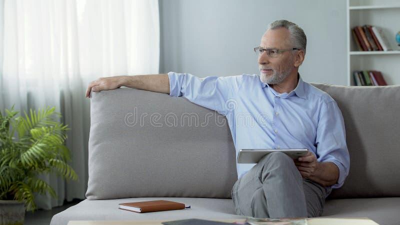 成功的老人坐有片剂的长沙发,使用工作的现代小配件 图库摄影