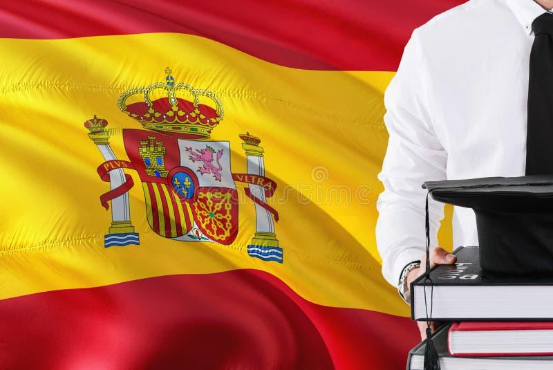 成功的西班牙学生教育概念 拿着书和毕业盖帽在西班牙旗子背景 库存照片