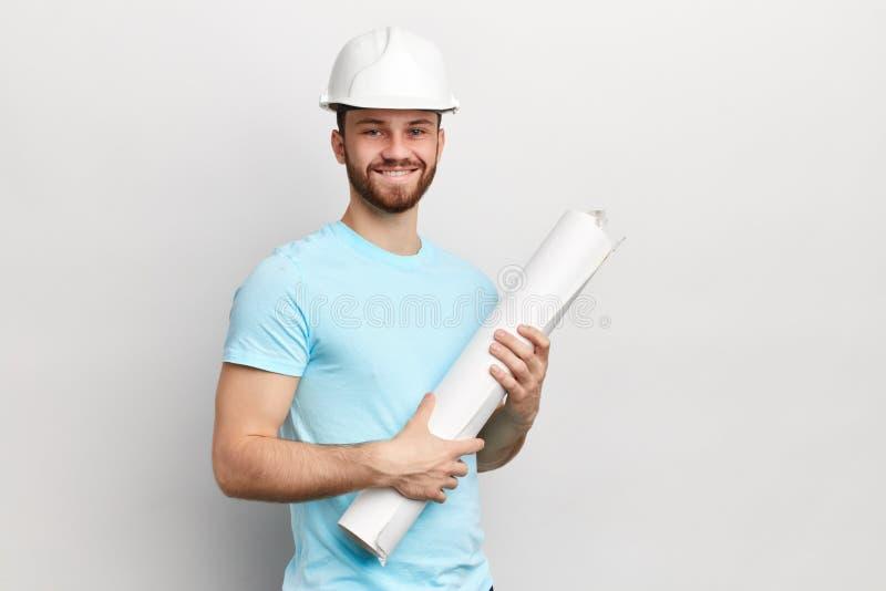 成功的逗人喜爱的英俊的建筑师是站立和拿着图纸 免版税库存图片