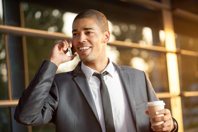 成功的非洲的商人谈话在机动性和微笑 库存图片