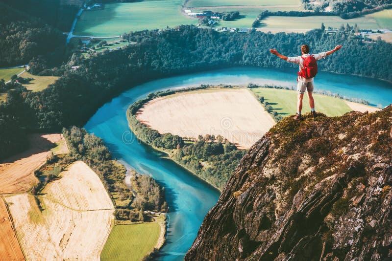 成功站立在峭壁的人背包徒步旅行者 免版税库存照片