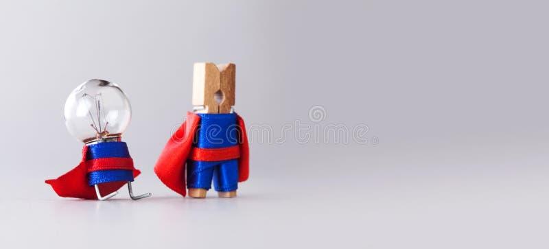 成功管理创造性的概念 特级英雄合作晒衣夹和电灯泡,在蓝色衣服的滑稽的玩具字符和 库存图片