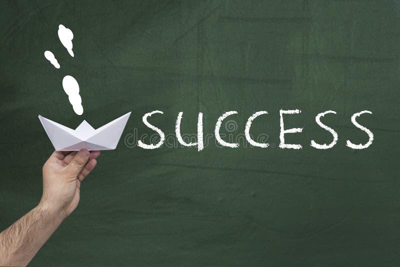 成功,成就概念 拿着纸船的人的手反对有词的绿色黑板:成功 库存照片