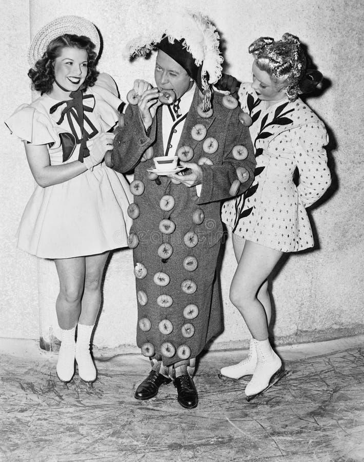 成套装备的人站立在两个十几岁的女孩之间的由油炸圈饼制成(所有人被描述不是更长的生存和没有庄园exis 免版税库存图片