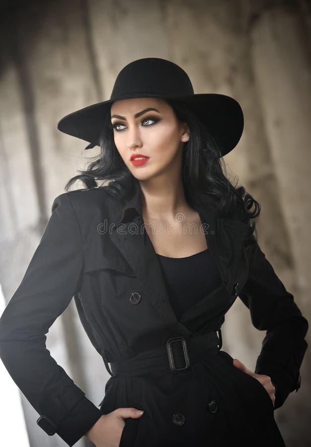 黑成套装备的,都市概念美丽的少妇 有摆在用在她的口袋的手的帽子的典雅的浅黑肤色的男人,室外 免版税库存图片