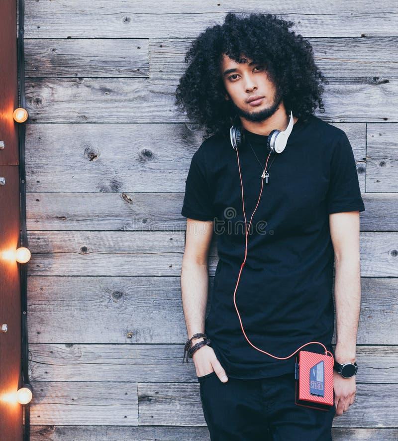 黑成套装备的年轻美国黑人的卷曲年轻人有耳机和红色葡萄酒卡式磁带播放机的老木背景的 免版税库存图片