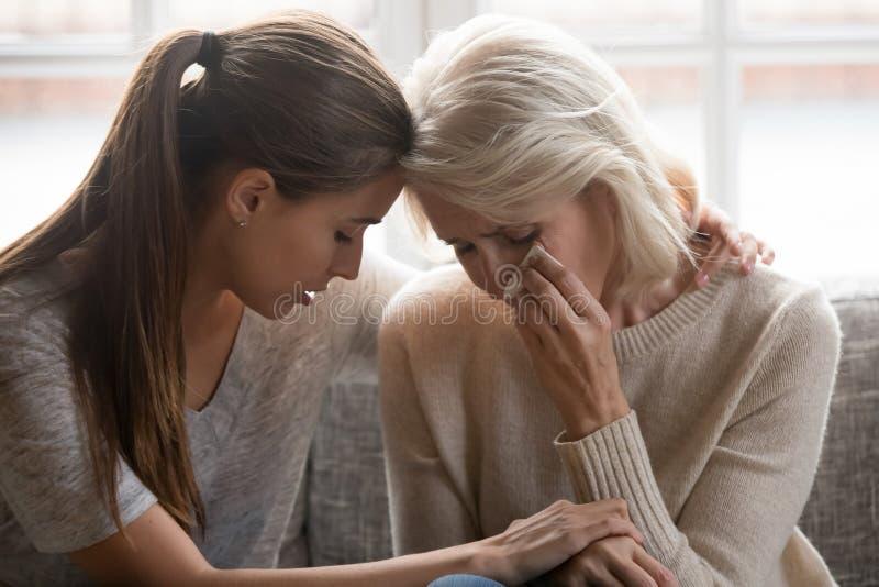 成年女儿安慰年迈的母亲举行她的手感觉同情 库存图片