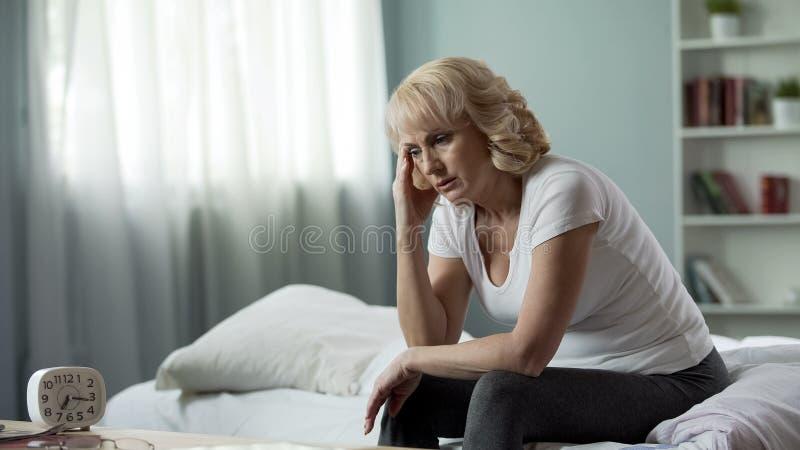 成年女性坐的床和遭受偏头痛,健康问题,更年期 免版税库存照片