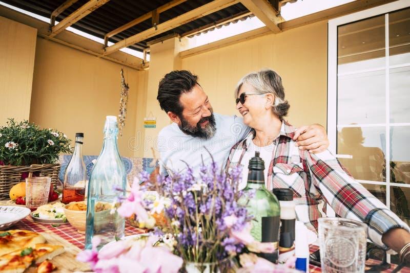成年家庭成员一起享受休闲活动,一起吃饭和玩乐-家里有食物和饮料-欢快 免版税库存图片