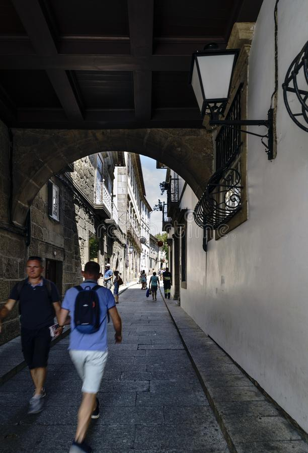 成拱形在城市的老部分的一条狭窄的鹅卵石街道上有漫步在树荫下的人的 免版税图库摄影