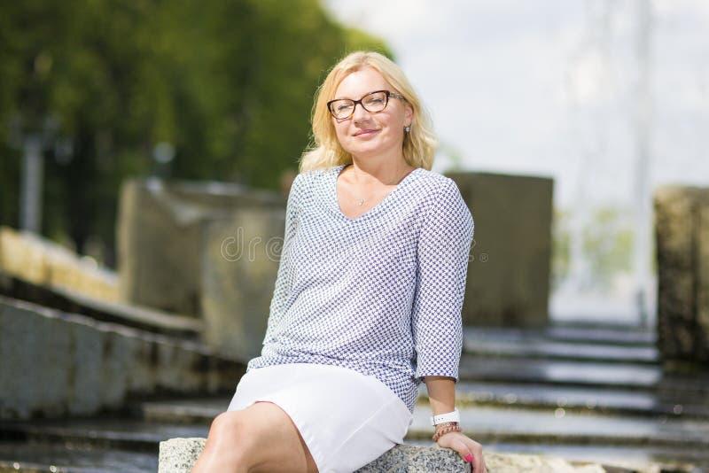 成熟中部画象变老了摆在微笑的白肤金发的妇女佩带的眼镜户外 免版税库存图片