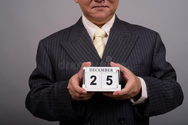 成熟亚洲商人藏品日历块agains的手 免版税库存照片