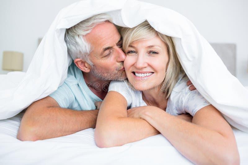 成熟人亲吻的妇女面颊特写镜头在床上 免版税库存照片
