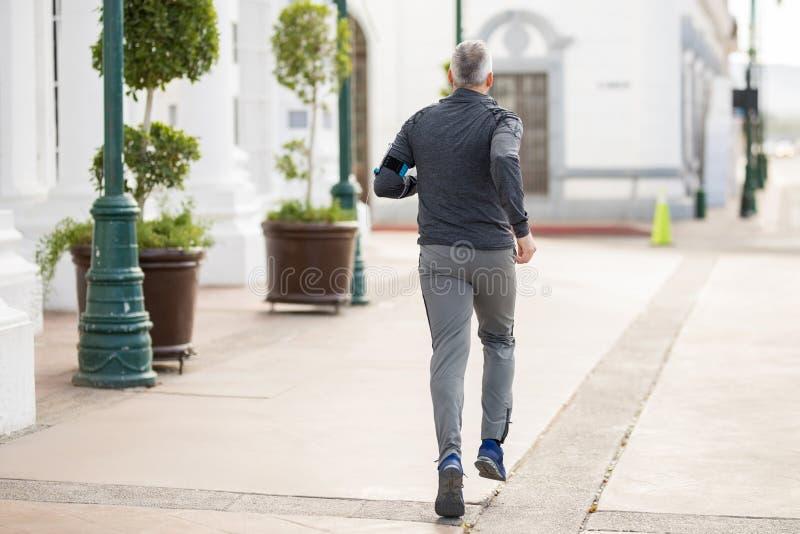 成熟人在一个早晨在城市跑 免版税库存图片